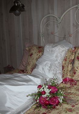 White satin wedding gown laid out on white iron bed with floral quilt and pink bouquet