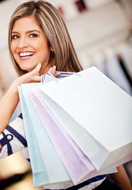 Smiling woman with shopping bags over her shoulder