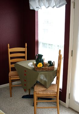 Small table with green tablecloth and two chairs rests a basket with coffee cups and carafe in this Burgundy room