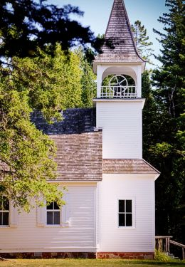 Pretty white wooden-sided church with shake roof surrounded by trees