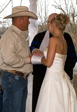 Country themed wedding with Cowboy groom and bride in white holding hands in front of officiant