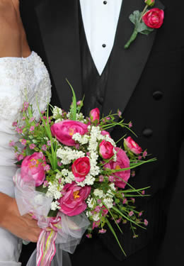 close up of bride's bouquet of magenta and white flowers with greenery.