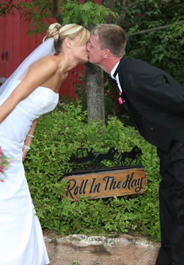 "Bride and Groom kissing in front of carved wooden ""Roll in the Hay"" signage surrounded by greenery."