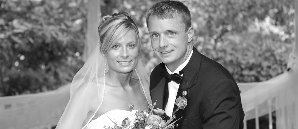 Black and white photo of blonde bride and groom smiling into camera