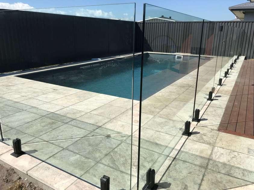 frameless glass pool fence mounted on black spigots