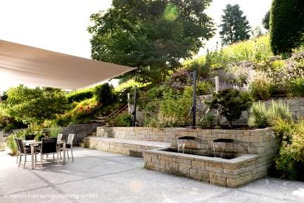 Terrassengarten mit Brunnen aus Naturstein, artenreiche Bepflanzung und gemütlicher Sitzplatz unter Sonnensegel