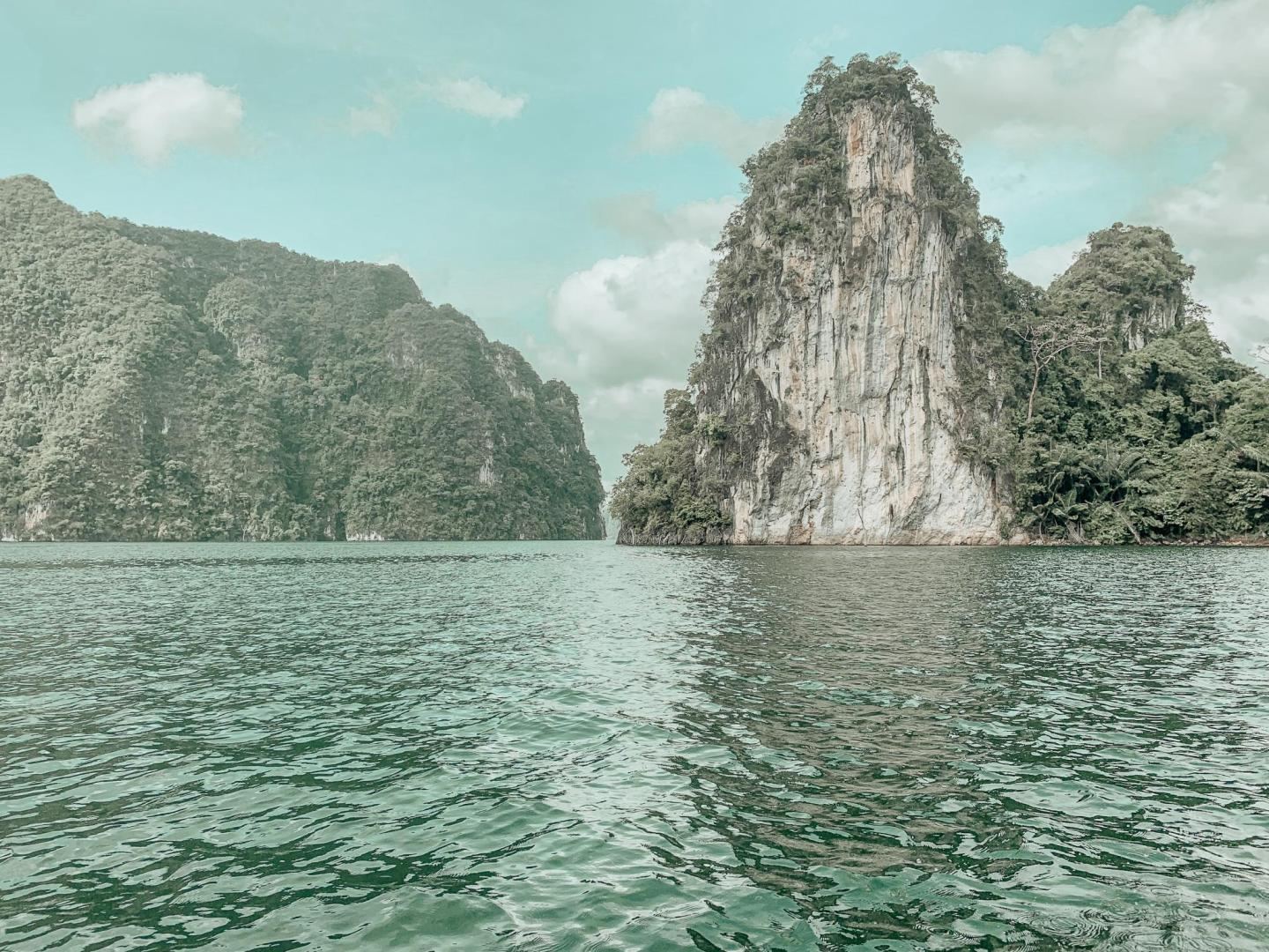 Clear blue skies and waters at Cheow Lan Lake in Thailand, the horizon is littered with limestone cliffs and islands that both fill and surround the lake, these are adorned with rain forest trees