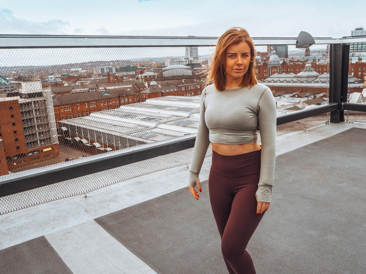 Emma is stood on a roof top in central Leeds with the city skyline behind her pondering are we sharing too much online