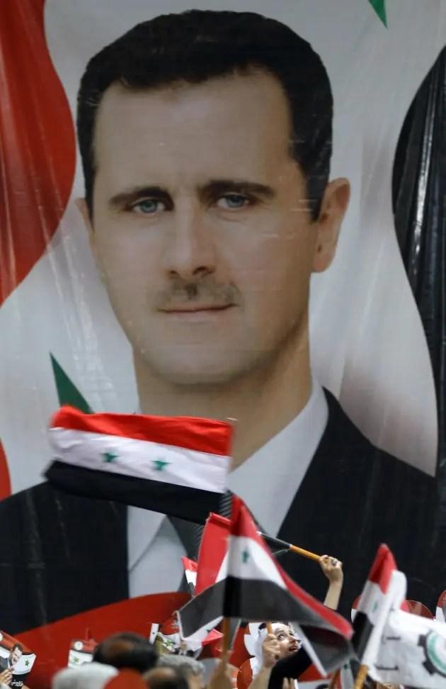 Damas, le 13 mai 2014. Un portrait géant de Bachar Al-Assad est déroulé lors d'un rassemblement de ses supporteurs. Celui-ci obtiendra un troisième mandat présidentiel, en juin 2014.