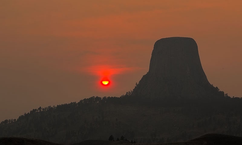 The sun sets in the smoke filled air.