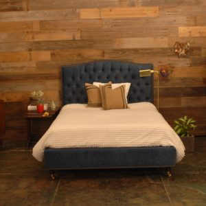 blue bed frame and a bed with w white textured blanket and decorative pillows