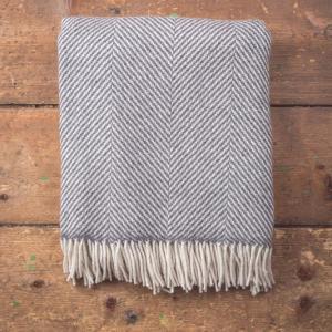 grey and white herringbone patterned blanket with tassels
