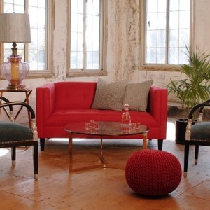 small red sofa and two chairs in a living room with plants and decor