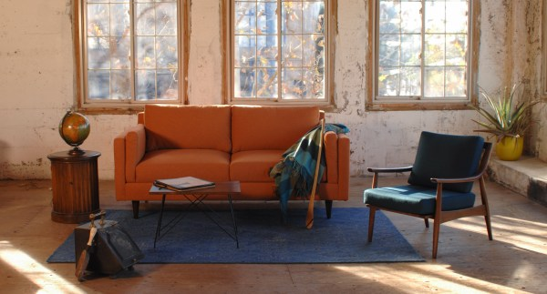 orange mid century modern style sofa in a living room with decor