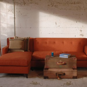 red mid century modern style sofa in a living room with furniture and decor