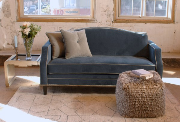 blue velvet sofa with grey trim and a side table with flowers