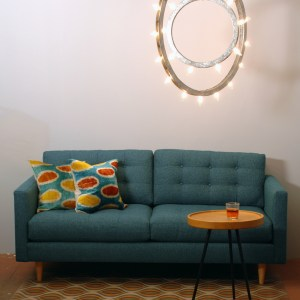 teal sofa and two decorative pillows