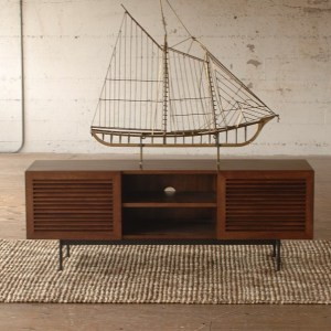 model ship on top of a wooden media console