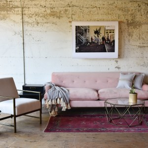 pink velvet sofa in a living room with furniture and decor