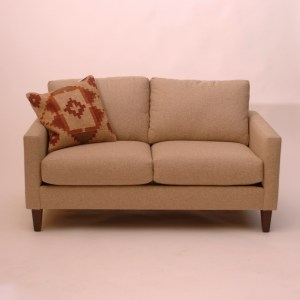 beige loveseat sofa and patterned pillow