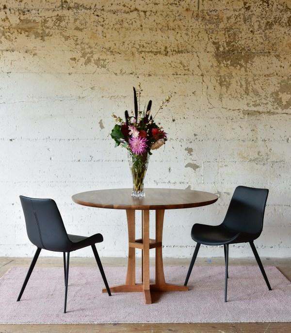 round wood dining table and black leather chairs