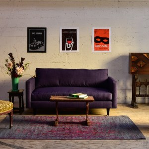 Purple sofa in living room with decor and plants