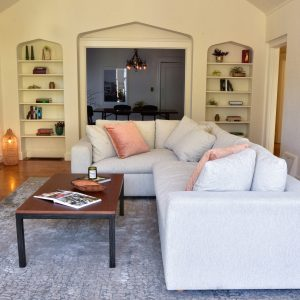Tan sofa in living room with decor and plants