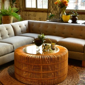 Rattan side table in living room with a grey sofa