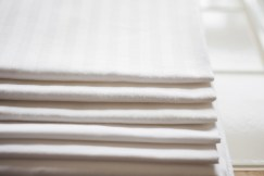 Stacked white ironed bed linen