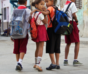 Uniformed schoolchildren head home after a day of classes.