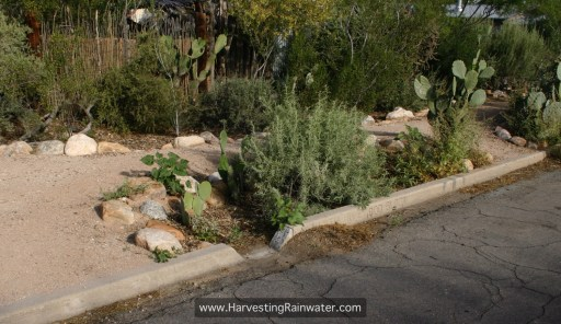 """Fig. 6. Finished curb cut and basin. Gravel and other sediment shoveled from street-curb gutter (on the upstream side of the curb cut) is placed on the downstream side of curb cut to help direct more flow into the basin. See """"Important Elevation and Slope Relationships"""" in chapter 8 for how this basin could be improved."""