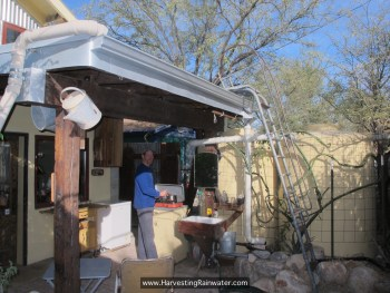 Figure 12. Garottage outdoor kitchen under east porch roof, and two 1,000-gallon rainwater tanks. Rainwater collected from 450-ft2 roof area provides all the water needed for the garottage in Tucson, Arizona, where 11 inches of rain falls in an average year. Water is distributed with a gravity-fed system—no pumps.