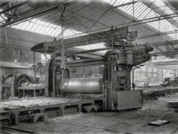 Bild: Das Breite Umkehr Walzwerk in Hettstedt aus dem Jahre 1909 in einer historischen Aufnahme. Links im Bild ist der Gleichstrommotor von SIEMENS SCHUCKERT zu sehen. In der Mitte das Walzgerüst vom GRUSONWERK Magdeburg. Die Walzen wiegen zusammen 70 Tonnen. Das Walzwerk ist ein Musterbeispiel damaliger deutscher Ingenieurkunst und wurde offensichtlich für die Ewigkeit projektiert - es läuft bis heute täglich - und begeistert auch jetzt noch jeden, der es in Aktion erleben darf. Dieses Bild ist gemeinfrei, weil seine urheberrechtliche Schutzfrist abgelaufen ist.