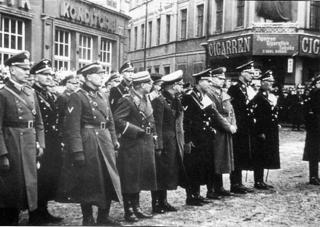 Bild: Aufmarsch der SS zum ersten Jahrestag des EISLEBER BLUTSONNTAGES. Der zweite von rechts ist der NSDAP Kreisleiter Ludolf von Alvensleben. Dieses Bild ist gemeinfrei, weil seine urheberrechtliche Schutzfrist abgelaufen ist.