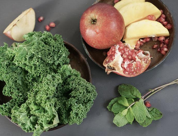 Zutaten für einen leckeren Grünen Smoothie aus Grünkohl, Minze, Apfel, Mango, Kokosmilch und Granatapfel