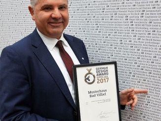 OKAL-Geschäftsführer Wilfried Bolz vor der Wand mit den Preisträgern des German Design Award 2017 (Foto: Markus Burgdorf)