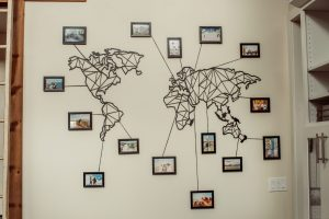 Metal world map laser cut with photo frames and lines pointing to destinations