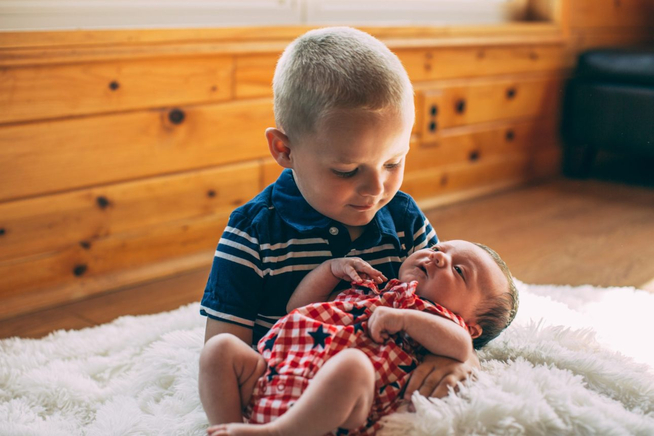 Henry holding his littler sister Claire for her newborn photos