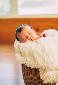 Newborn photo of Claire in a basket with fluffy blanket