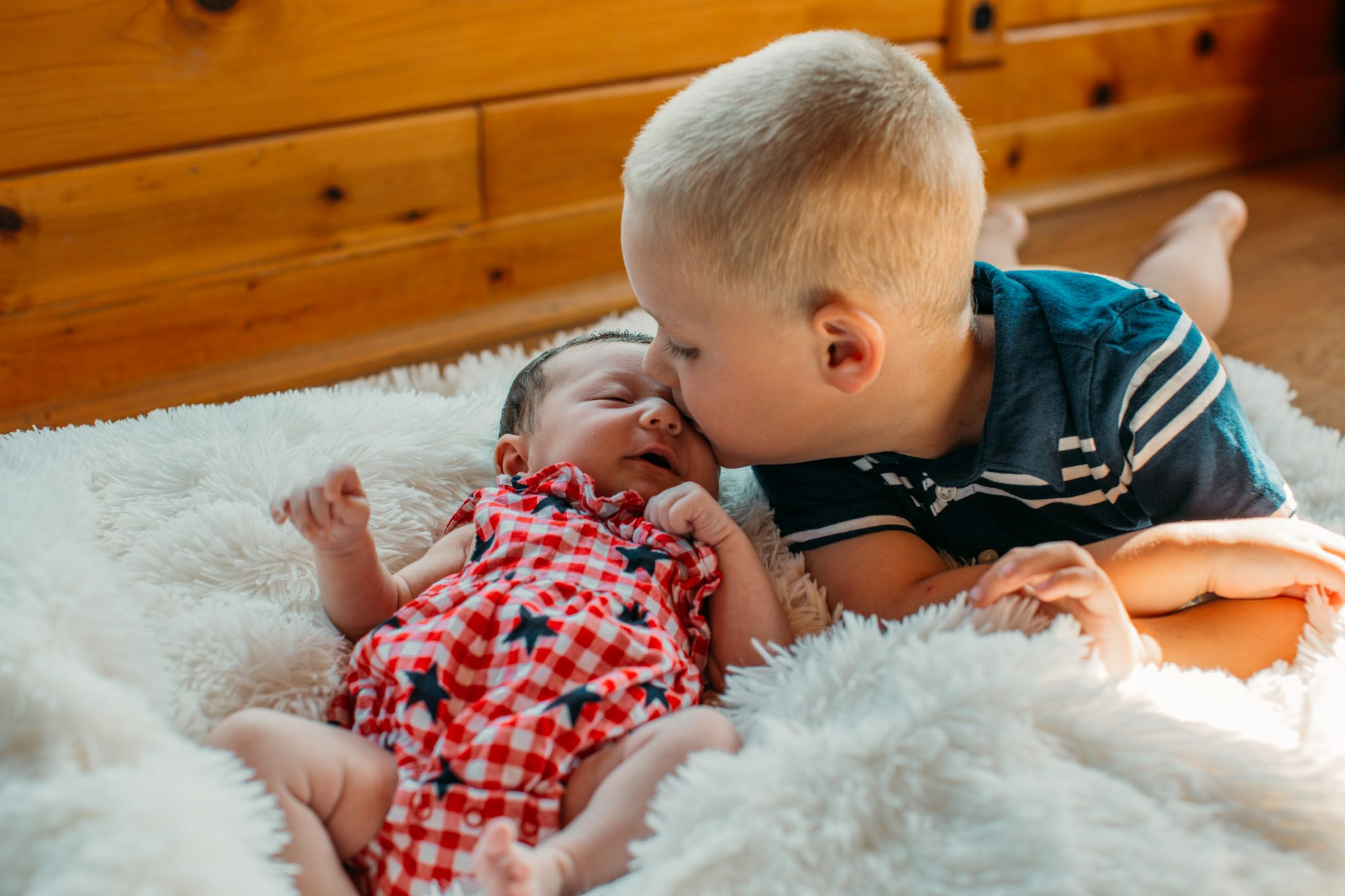 Henry kissing his littler sister Claire for her newborn photos