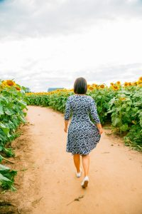 Wearing Karina Megan Dress in a sunflower field in Wisconsin