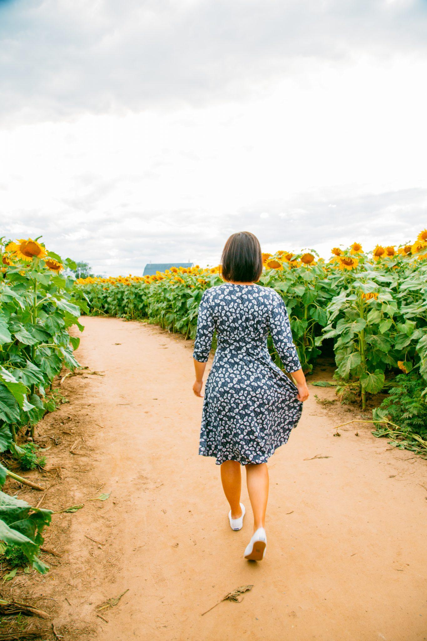 Wearing Karina Megan Dress in a sunflower field in Wisconsin