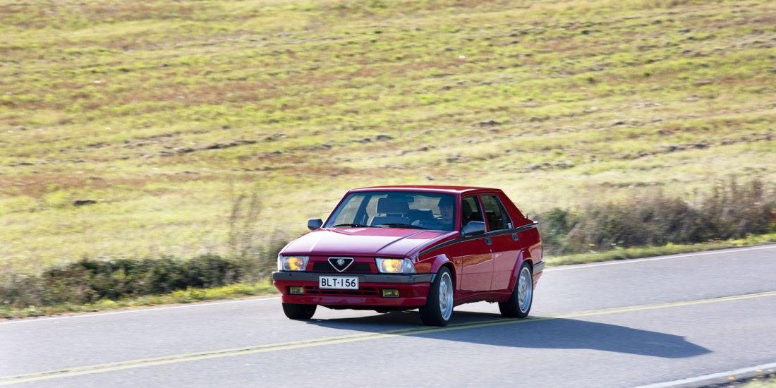 Alfa Romeo 75 mutkassa peltojen keskellä.