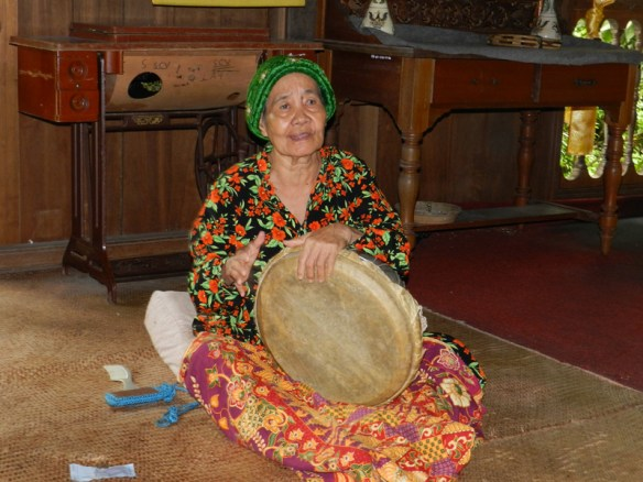 Woman playing a drum in the Malay house at the Sarawak Cultural Village, Bornreo.