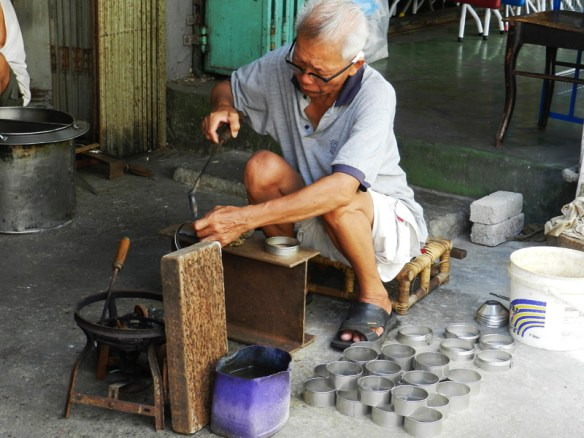 A tinsmith at work on the street outside his shop in Sarawak, Borneo.