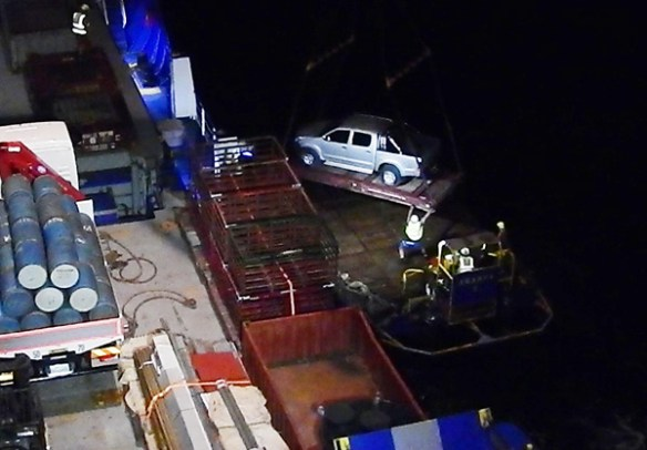 Aranui 5 sailors unoad a pick-up truck onto a barge at night for its trip to Tahuata wharf. Loading and unloading cargo usually takes place in daylight and is impressive even then. At night it's a great achievement.