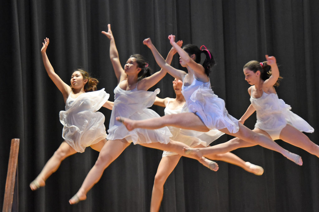 Five students jump in the air during a dance routine.