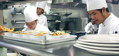 Culinary students preparing dishes in The Pearl restaurant kitchen