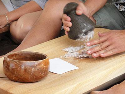 A hand pounding taro into poi