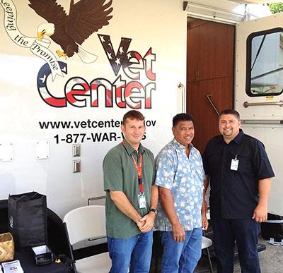 Three men in front of the Mobile Vet Center truck